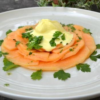 Un carpaccio de cantaloup avec de la glace au safran par-dessus dans une grande assiette blanche.
