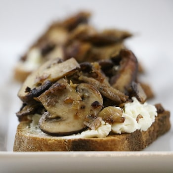 Des champignons sont déposés sur une tranche de pain.
