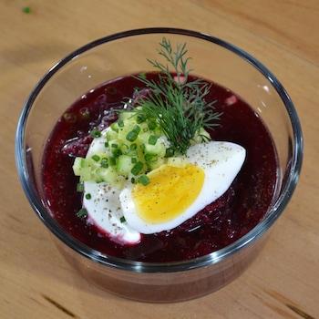 Une soupe de betterave avec un quartier d'œuf et de l'aneth dans un bol.