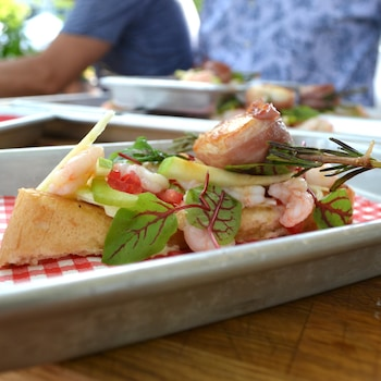 Guédilles aux crevettes dans une assiette blanche avec un papier à carreaux.