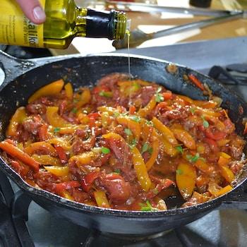 Chuck Hughes ajoute de l'huile d'olive à la recette de piperade qui chauffe dans la poêle.