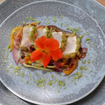 Dans une assiette grise,  filet de thon en croûte de wasabi et de riz soufflé en tempura décoré d'une fleur orange.