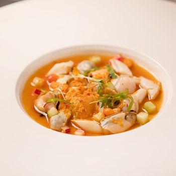 Coquillages, ponzu, concombres, shishito, fleurs de tagette et granité d'argousier servis dans une grande assiette profonde.