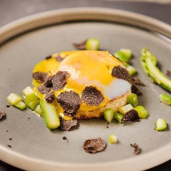 Une grande assiette avec au centre un oeuf basse température, asperges, croûton de brioche, croustilles de peau de poulet, sabayon au xérès et truffe noire.