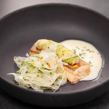 Un plat contenant une portion d'omble chevalier confit, yogourt, salade de fenouil et condiment crevettes, daikon et herbes.