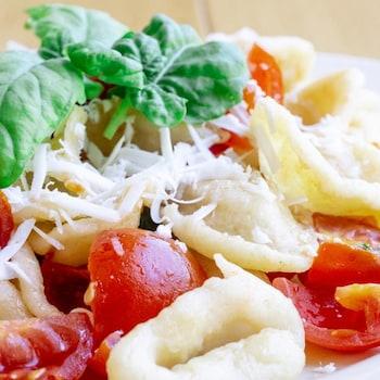 Orecchiette aux choux-fleurs et tomates cerises dans une assiette.