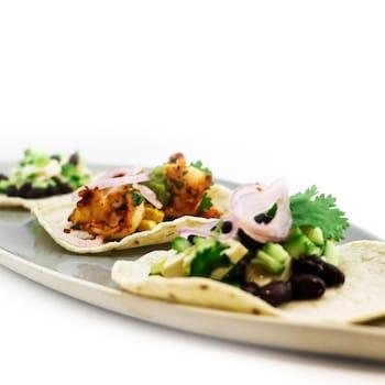 Trois tacos garnis dans un plat.