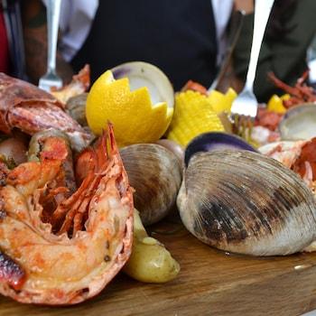 Des fruits de mer,  avec du citron et des légumes sur une planche de bois.