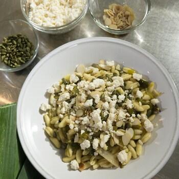 Un bol de pâtes avec des amandes grillées, des graines et du fromage émietté.