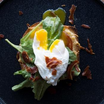 Une tranche de pain gratinée au four surmontée de pancetta, de roquette et d'un œuf poché coulant.