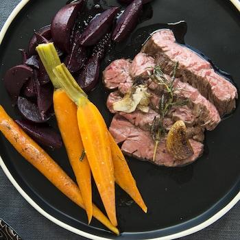 Une assiette avec des carottes cuites, des betteraves et du boeuf.