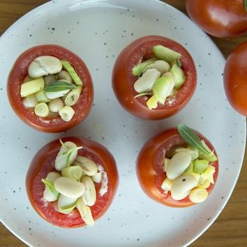 Une assiette avec 4 tomates farcies et des tomates sur vigne à côté.