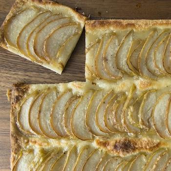 De la pâte recouverte de fines tranches de poire et dorée au four.