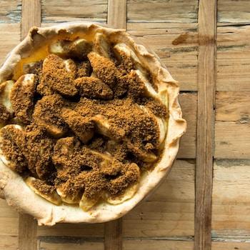 Une tarte aux pommes soupoudrée de canelle.