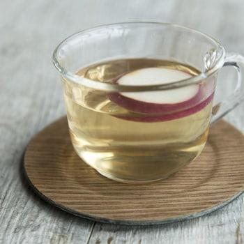 Une tasse de cidre chaud aux épices avec un quartier de pomme.