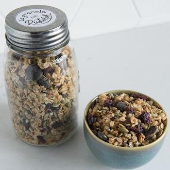 Un bol de granola est à côté d'un pot en verre.