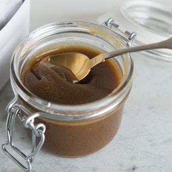 Une cuillère est plantée dans un pot de caramel.
