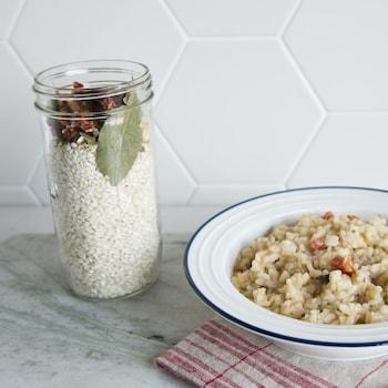 Un pot en verre avec les ingrédients du risotto est à côté d'un plat de risotto.