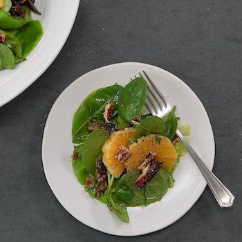 Une grande et une petite assiettes contiennent une salade d'épinards, d'agrumes et de pacanes.