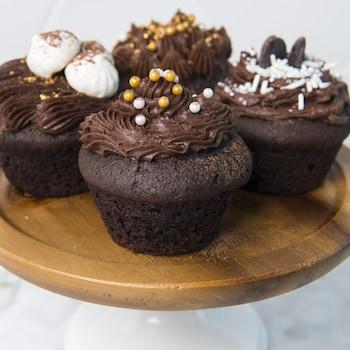 Quatre cupcakes sont sur une assiette sur pied.