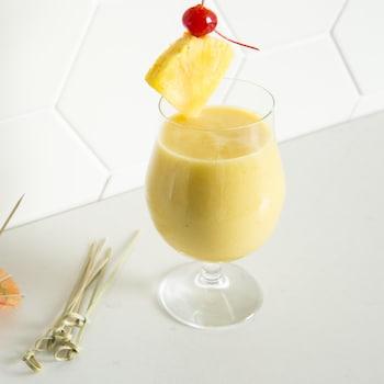 Le verre de pina colada est garni d'un morceau d'ananas et d'une cerise.