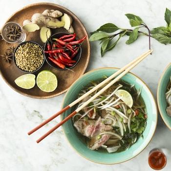 Deux bols de soupe et une assiette contenant les ingrédients sont déposés sur le comptoir.