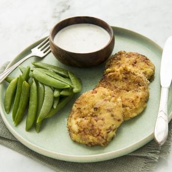 Trois croquettes sont disposées dans une assiette avec son accompagnement de sauce.