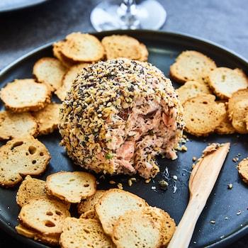 Une boulette de saumon fumé est au centre d'une assiette entourée de chips de bagel.