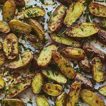 Des demies pommes de terre disposées sur une plaque de cuisson.