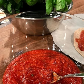 De la sauce tomate avec une cuillère.