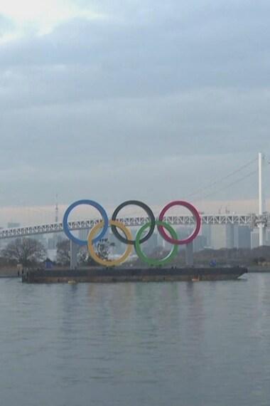 Les cinq anneaux olympiques sont sur une barge devant un grand plan d'eau.
