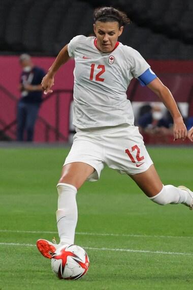 Une joueuse qui frappe le ballon de soccer lors des Jeux olympiques de Tokyo.