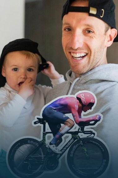 Un homme tient un bébé dans ses bras et sourit.