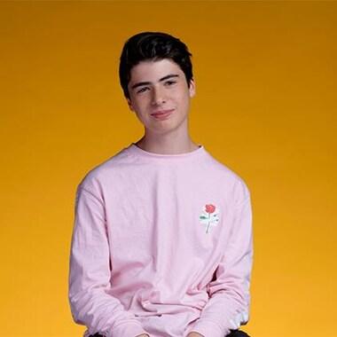 Mathias, tout sourire, est assis devant un fond orange.