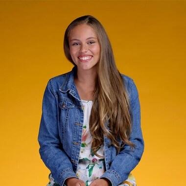 Audrey, tout sourire, se tient devant un fond orange.