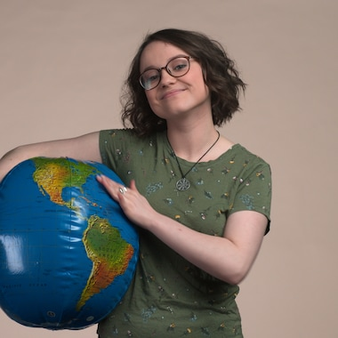 Romane tient sous son bras un ballon-planète et nous regarde.