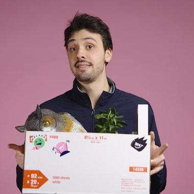 Thomas tient une boîte remplie d'objets en nous regardant.
