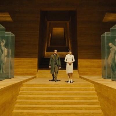 Deux personnages de Blade Runner 2049 déambulent dans une galerie de géants humanoïdes.