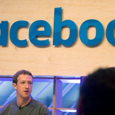 Une photo montrant Mark Zuckerberg en train de s'adresser à une foule, avec le logo de Facebook en arrière-plan.