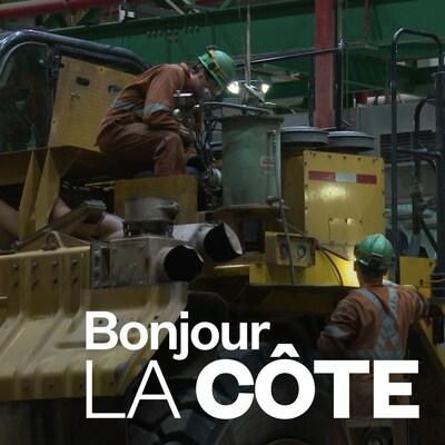 Des employés d'ArcelorMittal travaillent sur une machine dans un atelier de réparation.