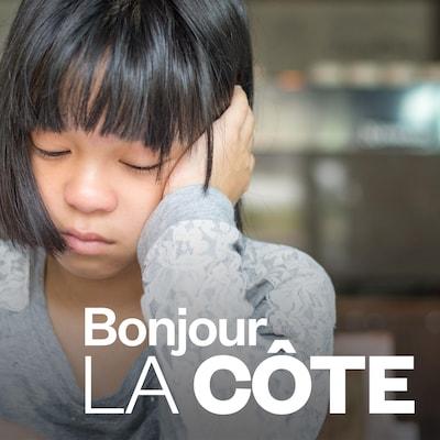 Une jeune fille, assise, repose sa tête sur sa main.