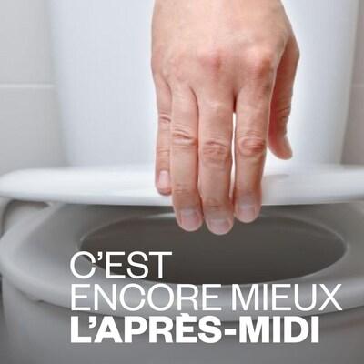 Une main ouvre la lunette des toilettes.