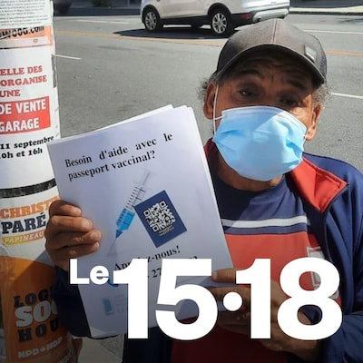 Un participant de l'organisme La Jarnigoine installe des affiches dans le quartier Villeray, pour aider les gens qui en ont besoin a obtenir leur passeport vaccinal.