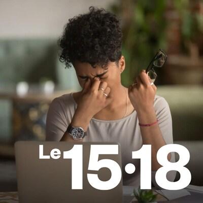 Une femme assise devant un ordinateur portable se frotte les yeux.