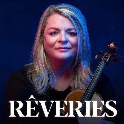 Une femme blonde posant de face, tenant un violon dans ses bras croisés