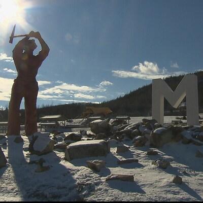 Un monument qui dépeint un mineur cassant de la roche près d'un grand M, pour Murdochville.