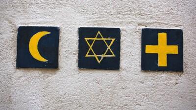Des symboles des trois plus importantes religions monothéistes, un croissant, une étoile et une croix, posés sur un mur en signe de paix.