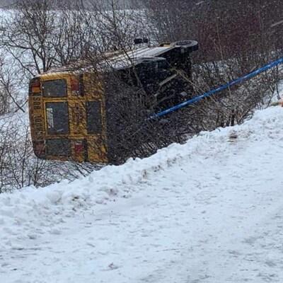 L'autobus scolaire sur le côté en bordure d'une route couverte de neige.