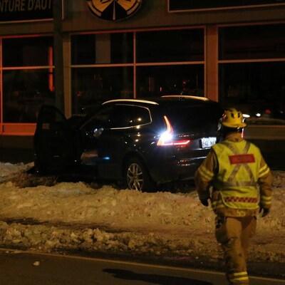 Un pompier s'approche de la voiture immobilisée, la porte ouverte
