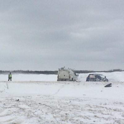 Une voiture gravement accidentée sur une route enneigée.